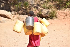The Water Project: Kyandoa Primary School -  Carrying Water Containers To The Scoop Hole