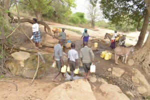 The Water Project: Kithoni Primary School -  Students And Community Members Fetching Water