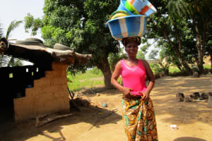 The Water Project: Targrin Health Post -  Woman Carries Containers At Household