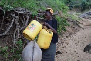 The Water Project: Kathungutu Community A -  Loading Water Onto Donkey