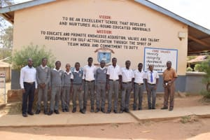 The Water Project: AIC Kyome Boys' Secondary School -  Students Pose In Front Of School Vision And Mission Sign
