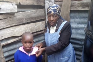 The Water Project: Banja Primary School -  A Little Girl At The Small Plastic Tank