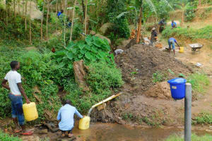 The Water Project: Bukhakunga Community, Khayati Spring -  People Fetching The Diverted Water During Construction