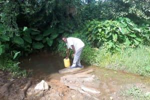 The Water Project: Kambiri Community, Sachita Spring -  Benjamin Sachita Fetching Water