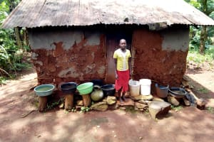 The Water Project: Mushina Community, Shikuku Spring -  Standing Outside Of Kitchen With Buckets For Collecting Rainwater