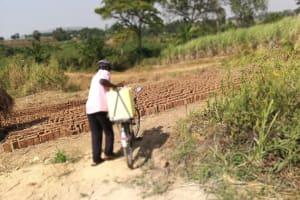 The Water Project: Kimigi Kyamatama Community -  Carrying Water On Bike