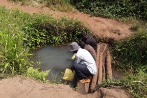 The Water Project: Kimigi Kyamatama Community -  Katusabe Gerald Fetching Water From The Open Well
