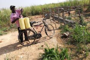The Water Project: Kimigi Kyamatama Community -  Loading Water Containers Onto Bike