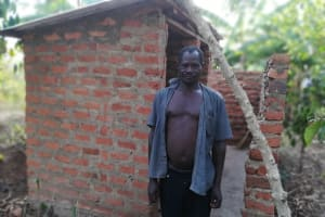The Water Project:  Man Poses In Front Of Latrine
