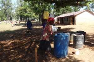 The Water Project: Irobo Primary School -  Women Delivering Water To Mix Cement