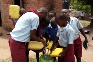 The Water Project: Kipchorwa Primary School -  Filling A Barrel