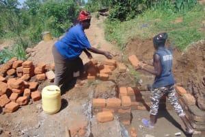 The Water Project: Musango Community, Mwichinga Spring -  Woman Helping The Artisan
