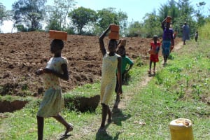 The Water Project: Kambiri Community, Sachita Spring -  Community Members Carrying Bricks To The Site