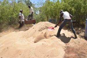 The Water Project: Mbau Community C -  Shoveling Sand That Is Used To Mix With Cement
