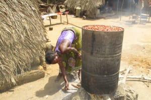 The Water Project: Lokomasama, Musiya, Nelson Mandela Secondary School -  Old Woman Cooking Palm Kernels