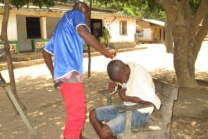 The Water Project: Lokomasama, Musiya, Nelson Mandela Secondary School -  Young Boy Giving Haircut To Friend
