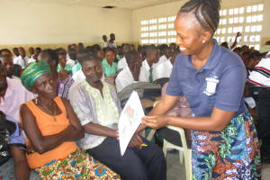 The Water Project: UBA Senior Secondary School -  Hygiene Facilitator Showing Bad Hygiene Poster To A Community Member