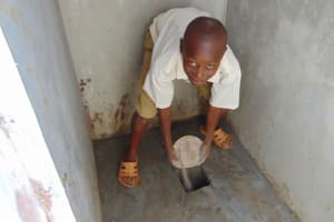 The Water Project: Essongolo Primary School -  Pouring Ash In The Latrine Pits