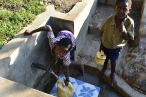 The Water Project: Munenga Community, Burudi Spring -  Enjoying Fetching Water
