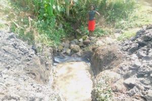 The Water Project: Munenga Community, Burudi Spring -  Field Officer Checks Progress