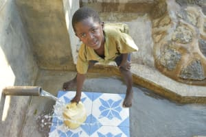The Water Project: Munenga Community, Burudi Spring -  Young Boy Fecthes Water
