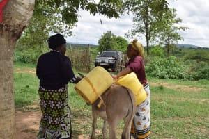 The Water Project: Kaketi Community -  Loading Water Onto Donkey