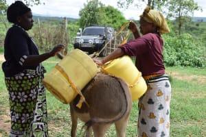 The Water Project: Kaketi Community A -  Loading Water Onto Donkey