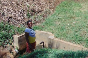 The Water Project: Esembe Community, Chera Spring -  Linet Fetches Water