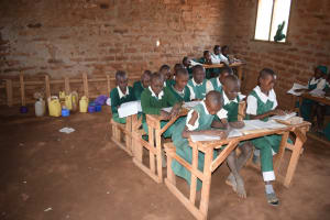 The Water Project: Kangutha Primary School -  Students In Class With Their Containers Of Water In The Back