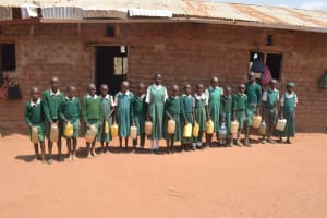 The Water Project: Kangutha Primary School -  Students Lined Up Holding Their Containers Full With Water