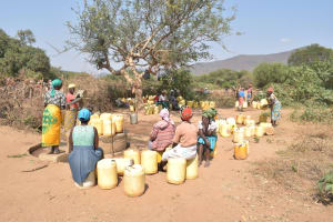 The Water Project: Nyanyaa Secondary School -  Women Sit On Their Containers Waiting For Their Turn To Fill Them With Water