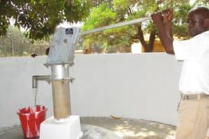 The Water Project: DEC Makassa Primary School -  The Head Teacher Pumps Water