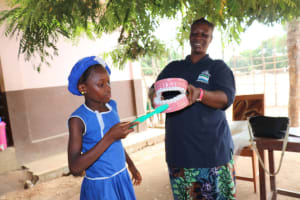 The Water Project: Mahera, SLMB Primary School -  A Student Helps In The Toothbrushing Demonstration