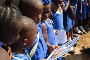 The Water Project: Mahera, SLMB Primary School -  Pupils Looking At Jediah Ballard Picrures