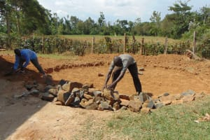 The Water Project: Bululwe Secondary School -  Adding Rock Layer