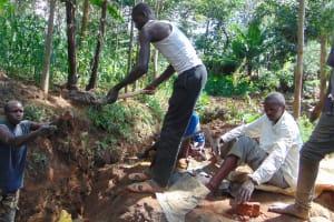 The Water Project: Buhayi Community, Nasichundukha Spring -  Community Members Help Pass Cement