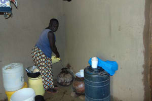 The Water Project: Munenga Community, Francis Were Spring -  Pouring Drinking Water Into Clay Pot For Storage