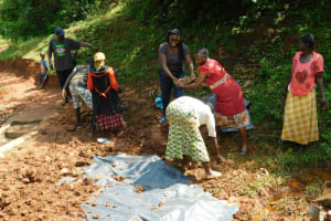 The Water Project: Mutao Community, Kenya Spring -  Women Helping Out At The Spring
