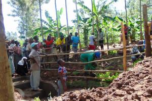The Water Project: Buhayi Community, Nasichundukha Spring -  Artisan Helps Plant Flowers