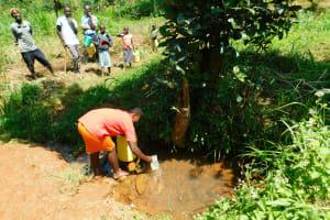 The Water Project: Ewamakhumbi Community, Mukungu Spring -  People Wait To Fetch Water