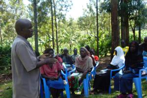 The Water Project: Buhayi Community, Nasichundukha Spring -  Community Member Leads An Activity