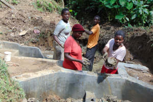 The Water Project: Shamiloli Community, Kwasasala Spring -  Women Deliver Clay Before Backfilling