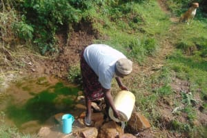 The Water Project: Mukangu Community, Metah Spring -  Selestine Washes Her Container