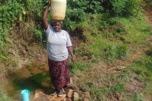 The Water Project: Mukangu Community, Metah Spring -  Selestine Carries Water Home