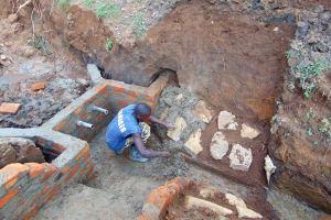 The Water Project: Buhayi Community, Nasichundukha Spring -  Adding The Stone Wall