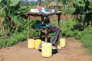 The Water Project: Kalenda A Community, Webo Simali Spring -  Child At The Dishrack Outside The House