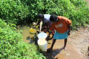 The Water Project: Kalenda A Community, Webo Simali Spring -  Community Members Fetching Water