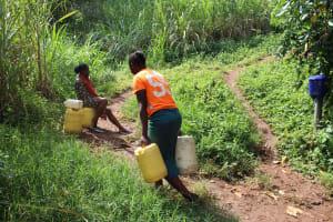The Water Project: Imbinga Community, Imbinga Spring -  Hauling Water