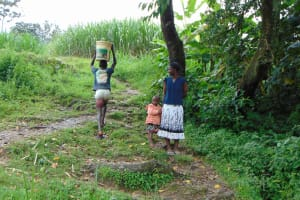 The Water Project: Buyangu Community, Mukhola Spring -  Carrying Water From Spring