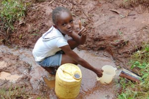 The Water Project: Masuveni Community, Masuveni Spring -  Child Collects Water